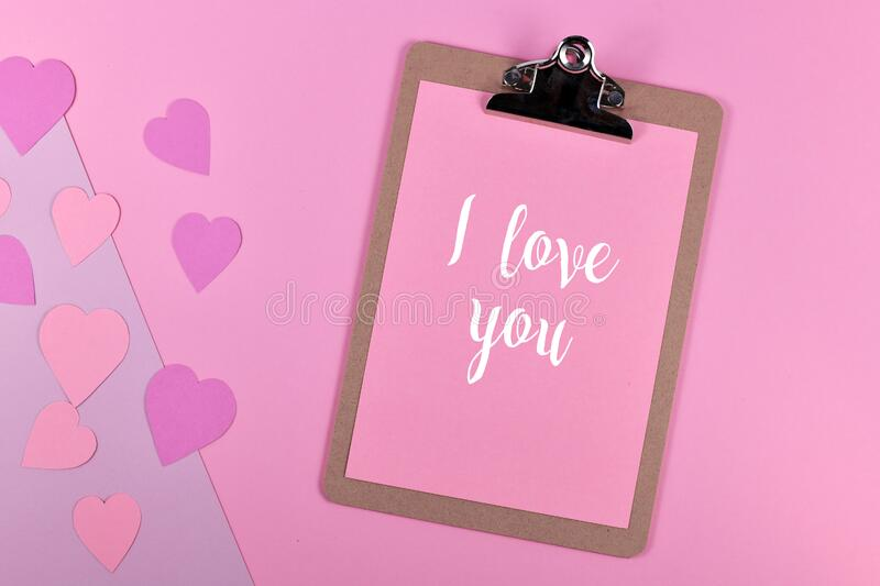 Romantic Valentine`s Day flatlay with clipboard with text `I love you` and paper hearts on pink background. Cute romantic Valentine`s Day flatlay with clipboard royalty free stock photo