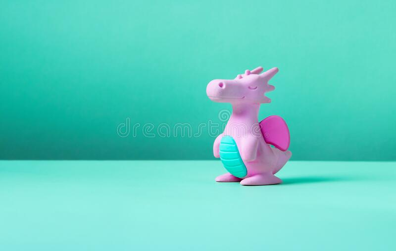 Cute rubber dragon toy. On green background stock photography