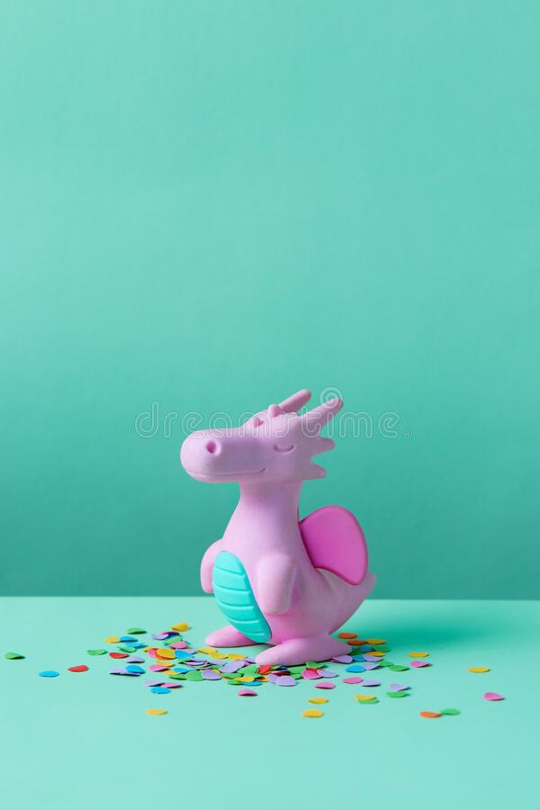 Cute rubber dragon toy on green background. Cute rubber dragon toy with confetti on green background royalty free stock photography