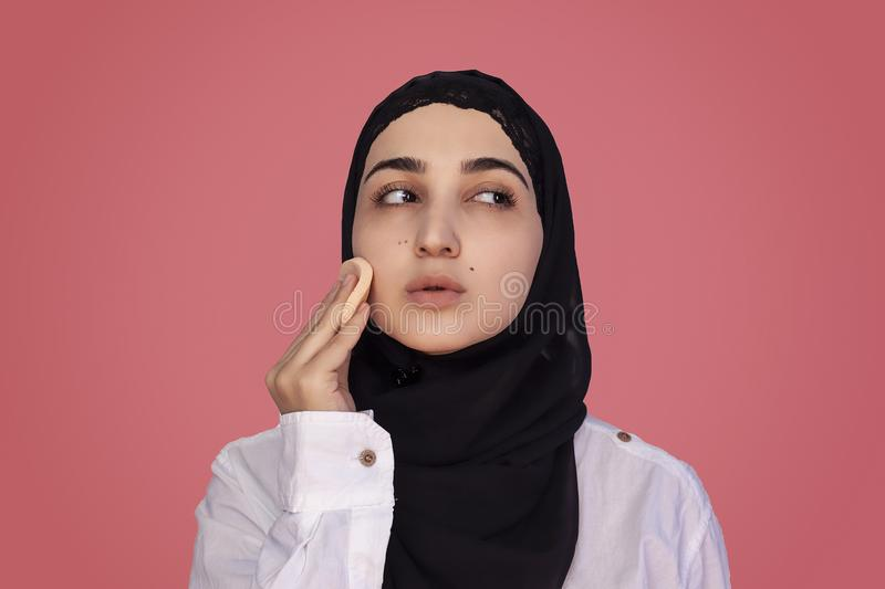 Cute 20s female applying applying powder with sponge on her face. Beautiful Persian woman in hijab doing make-up stock photo