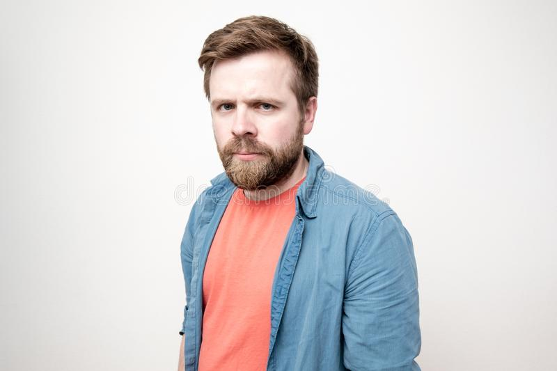 Cute, sad, bearded man looks upset and gloomy at the camera, on a white background royalty free stock image
