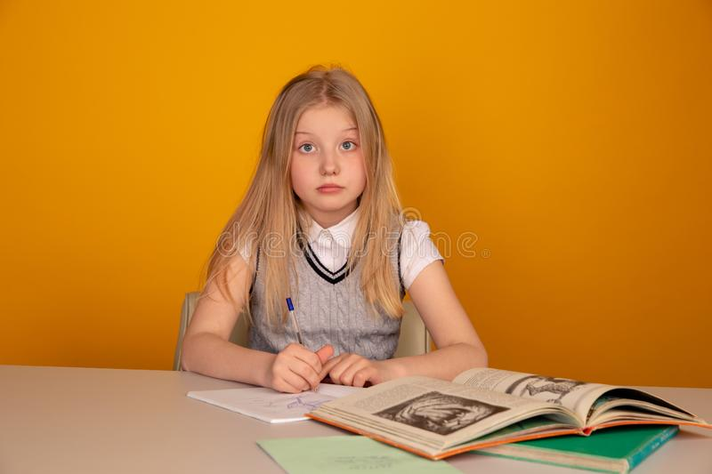 Cute and sad little girl doing homework in the bricht yellow room. stock photos