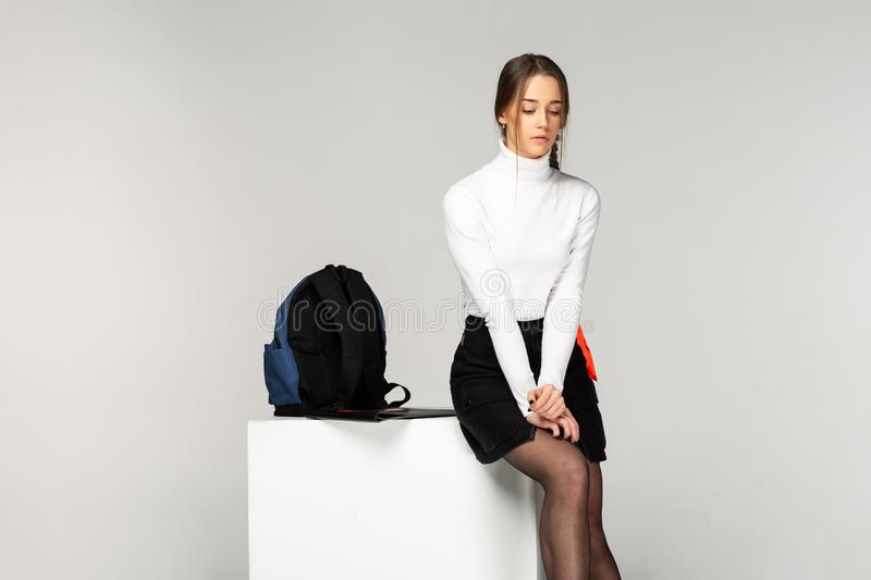 Cute sad schoolgirl sitting on white cube near a backpack royalty free stock photos