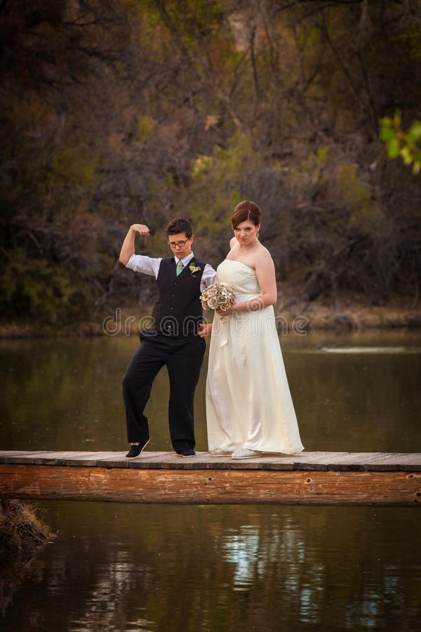 Cute Same Sex Couple on Dock. Macho lesbian groom with bride on dock over pond royalty free stock photo