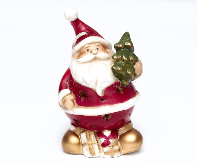 Cute Santa Claus doll with a Christmas tree in his hand. Adorable Santa Claus decorative toy, insulator on a white background. Cute Santa Claus doll. Adorable royalty free stock images