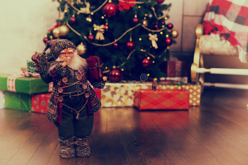 Cute Santa Claus doll wearing traditional costume and holding a. Cute Santa Claus doll with a blush on the cheeks wearing traditional costume and holding a gift stock photography