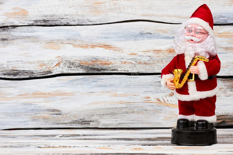 Cute Santa Claus puppet and copy space. Santa Claus doll with saxophone standing on old wooden background, space for text royalty free stock image