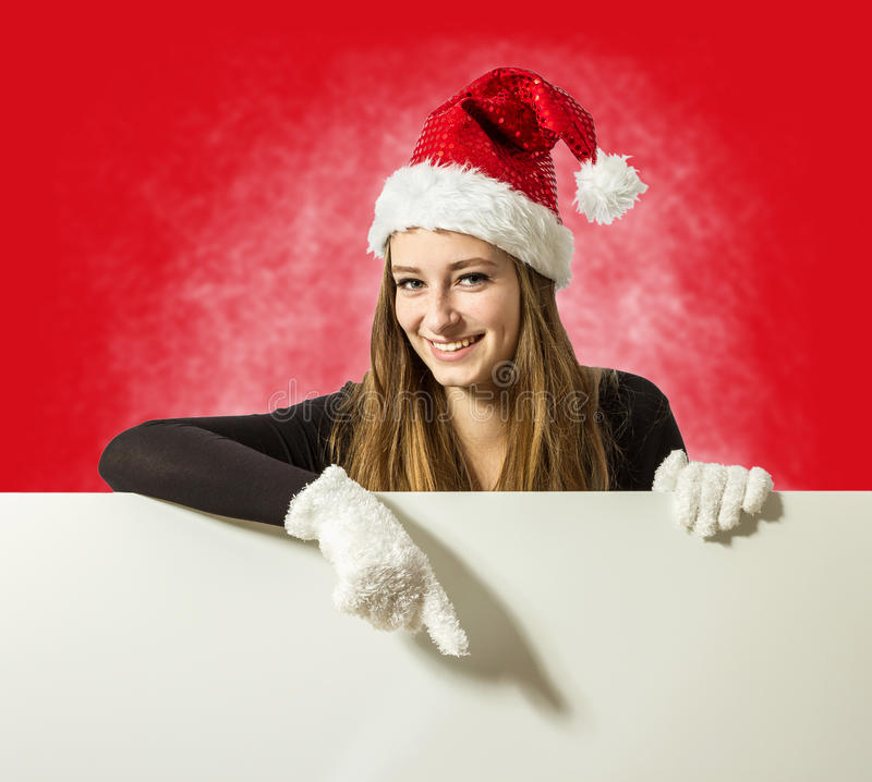 Cute santa girl presenting something on white writing board royalty free stock photography