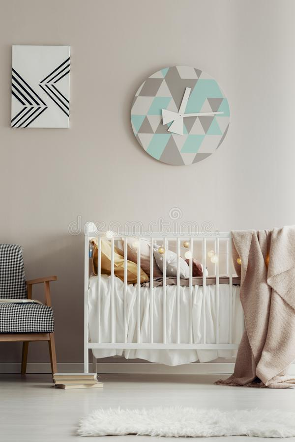 Cute, scandi bedroom interior for a child with a white crib, pastel wall and a round clock. Real photo royalty free stock photos