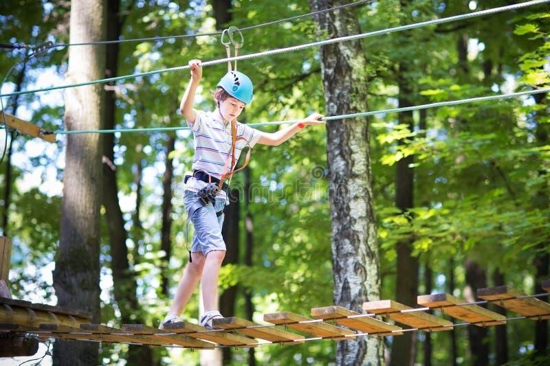 Cute school boy in a climbing activity park stock photos