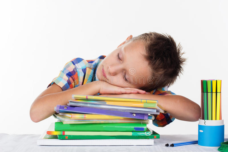 Cute school boy is dreaming on books. Tired schoolboy sleeping on books pile, isolated over white background stock photography