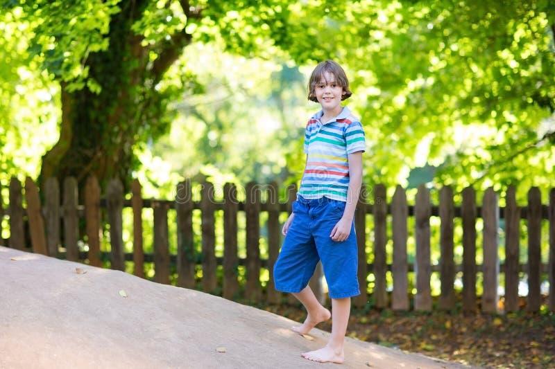 Cute school boy on playground on hot sunny day stock photo