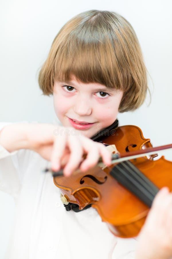 Cute school boy playing violin, close up portrait stock photo