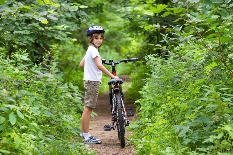 Cute school boy riding a bike in summer park stock photo