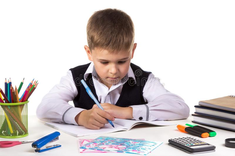 Cute school boy sitting at the desk, writing, surrounded with stationery royalty free stock photography