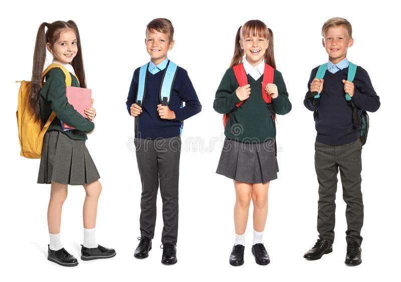 Cute school children in uniform with backpacks royalty free stock photo