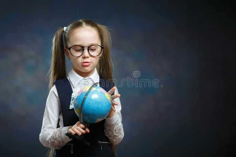 Cute School Girl in Uniform Rotate World Globe. Preschooler Hold Geography Studing Tool in Hand. Beautiful Little Kid with two Long Ponytail in Formal Wear royalty free stock photo