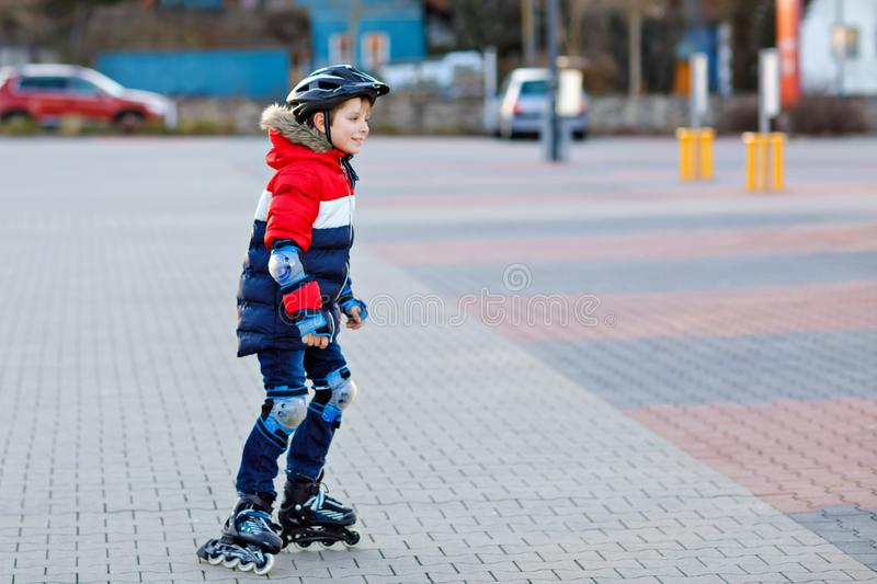 Cute school kid boy skating with rollers in the city. Happy healthy child in protection safety clothes skating with. Rollers. Active schoolboy making sports and royalty free stock photo