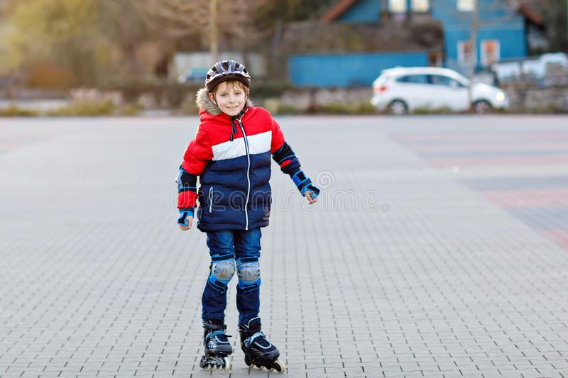Cute school kid boy skating with rollers in the city. Happy healthy child in protection safety clothes skating with stock photo