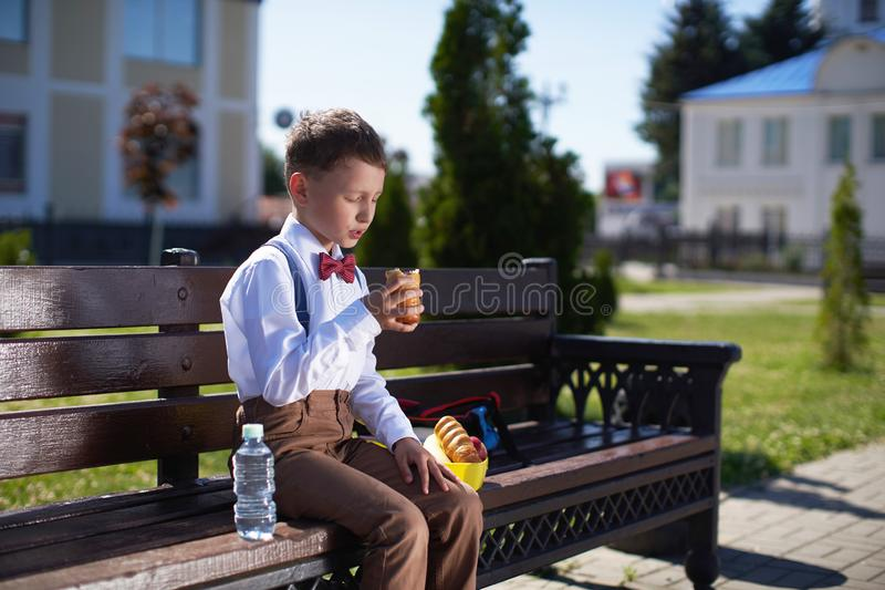 Cute schoolboy eating outdoors the school. Healthy school breakfast for child. Food for lunch, lunchboxes with sandwiches, fruits royalty free stock photos