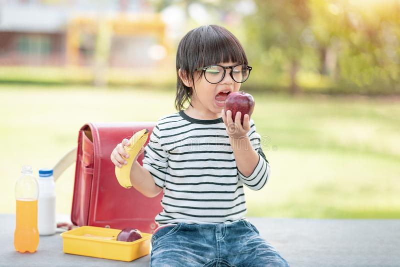 Cute schoolboy eating outdoors the school from plastick lunch boxe. Healthy school breakfast for child. Food for lunch, Lunchboxes royalty free stock photos