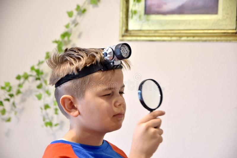 Young Caucasian boy with head torch lamp looking through a magnifier glass stock image
