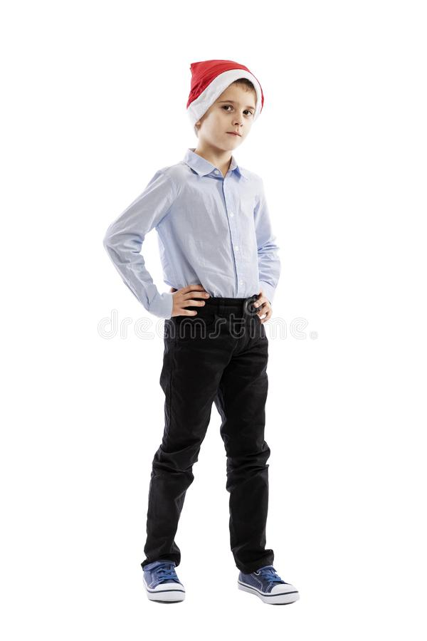 A cute schoolboy in a Santa Claus hat is standing. Full height. Isolated over white background. stock image