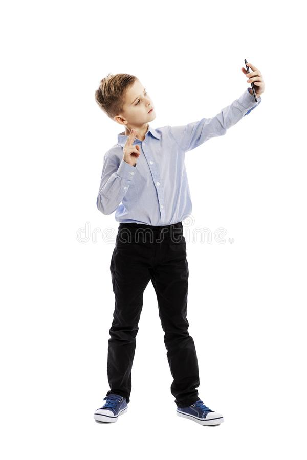 Cute schoolboy in trousers and a blue shirt takes a selfie. Full height. Isolated over white background. stock photography