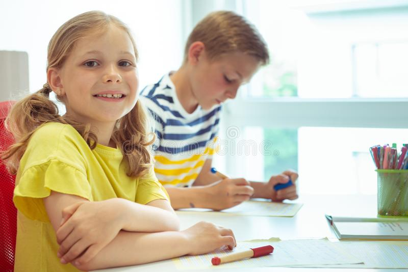 Cute schoolchildren are came back to school and learning at the table in classroom stock image