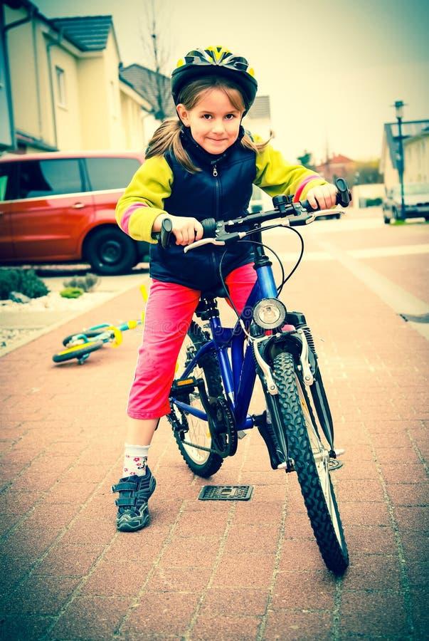 Cute schoolgirl on the bike. Cute schoolgirl with helmet on the bike stock photos