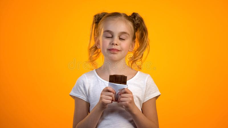 Cute schoolgirl enjoying taste of delicious chocolate, happy childhood, emotions royalty free stock images