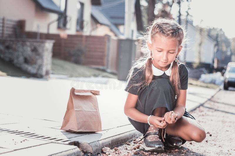 Cute schoolgirl gathering chestnuts in the street on the way home. Gathering chestnuts. Cute dark-haired schoolgirl gathering chestnuts in the street on the way stock photo