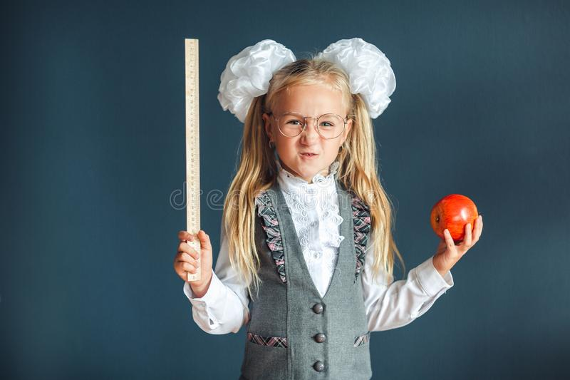 Cute schoolgirl with glasses and red Apple in hand looking like a strict teacher raised her pointer to draw attention. Educational royalty free stock photo