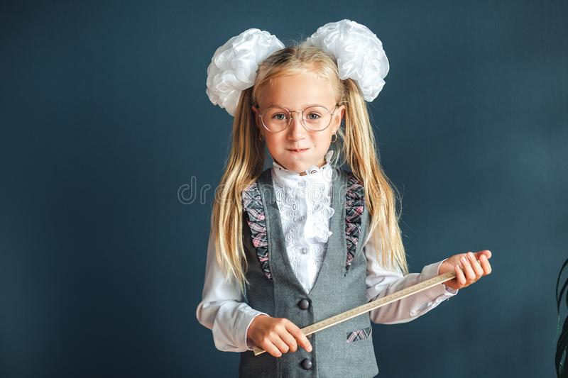 Cute schoolgirl with glasses and ruler looking like a strict teacher raised her pointer to draw attention. Educational concept. stock photo
