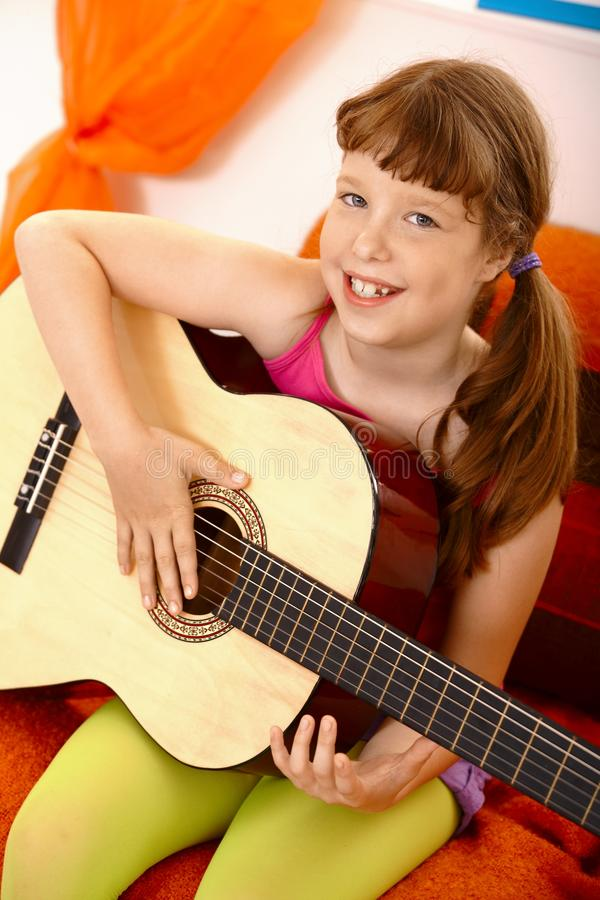 Cute schoolgirl with guitar stock images