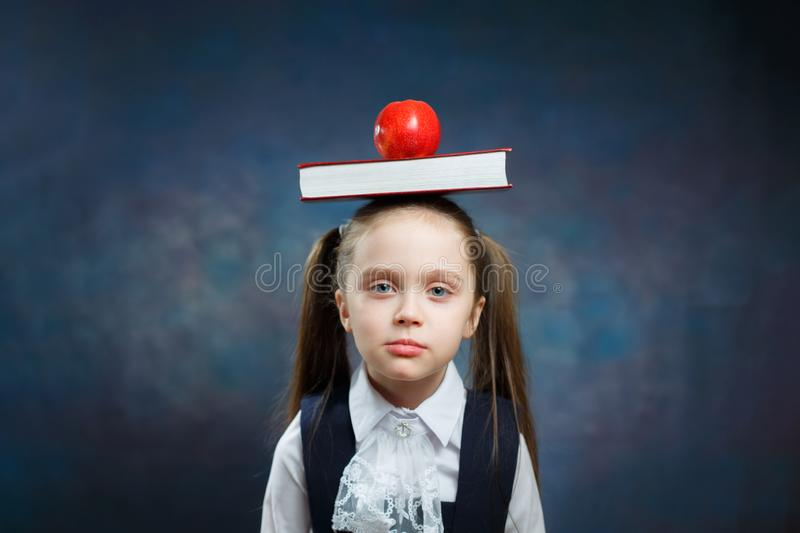 Cute Schoolgirl Hold Book Apple on Head Portrait royalty free stock photography