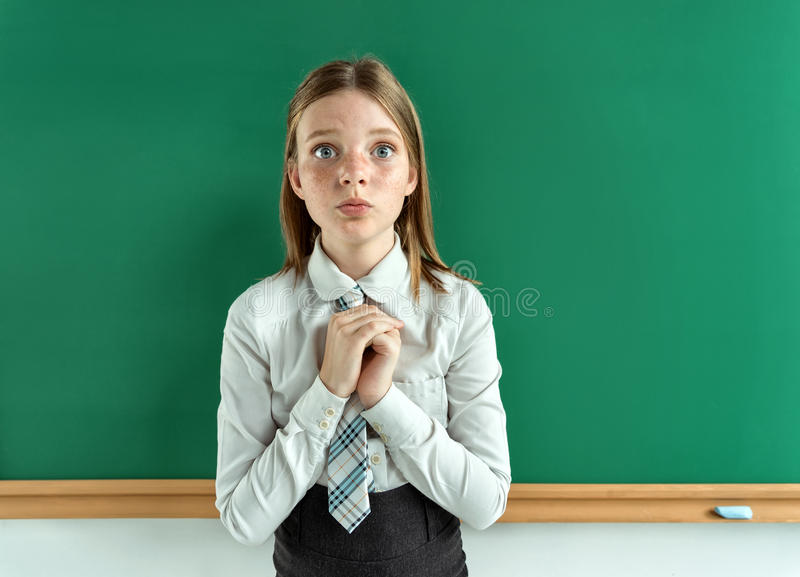 Cute schoolgirl near blackboard with folded hands. In anticipation of something. Photo of teen school girl, creative concept with Back to school theme stock image