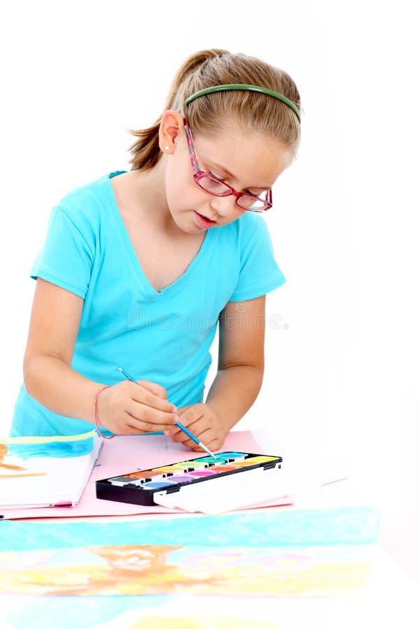 Cute schoolgirl painting stock image