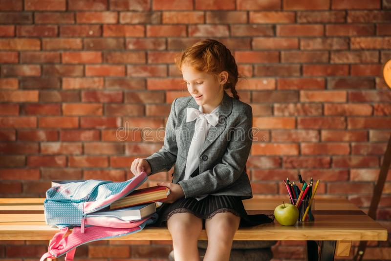 Cute schoolgirl puts textbook into the schoolbag royalty free stock photo