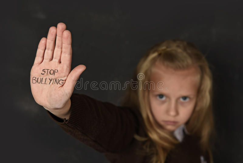 Cute schoolgirl scared sad asking for help showing hands with stop bullying text written on her palm. Young little cute schoolgirl scared and sad asking for help royalty free stock photography