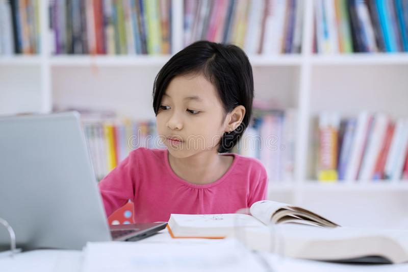 Cute schoolgirl using a laptop in the library royalty free stock photos