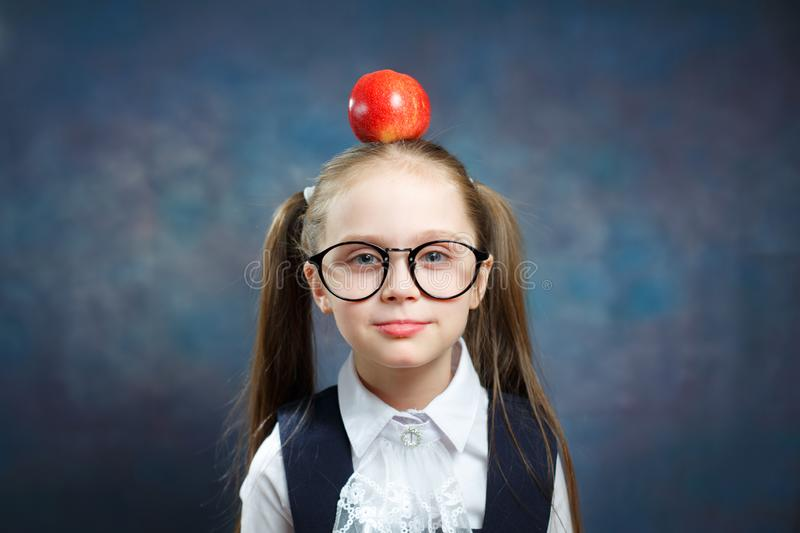 Cute Schoolgirl Wear Glasses Hold Apple on Head stock photo