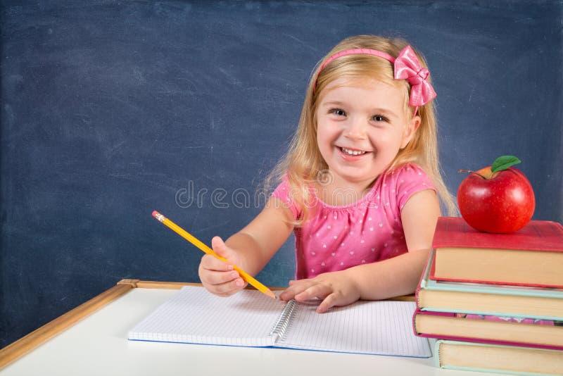 Cute schoolgirl writing on copybook royalty free stock image