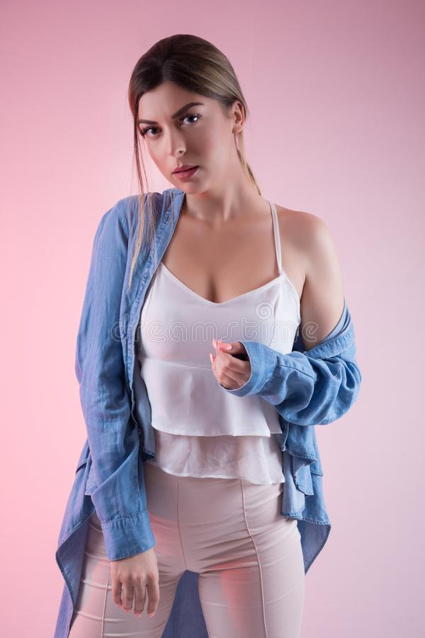 Seductive young woman with bare shoulder wears blue jeans shirt isolated on pink background in studio. Cute and seductive young female with bare shoulder wears stock images
