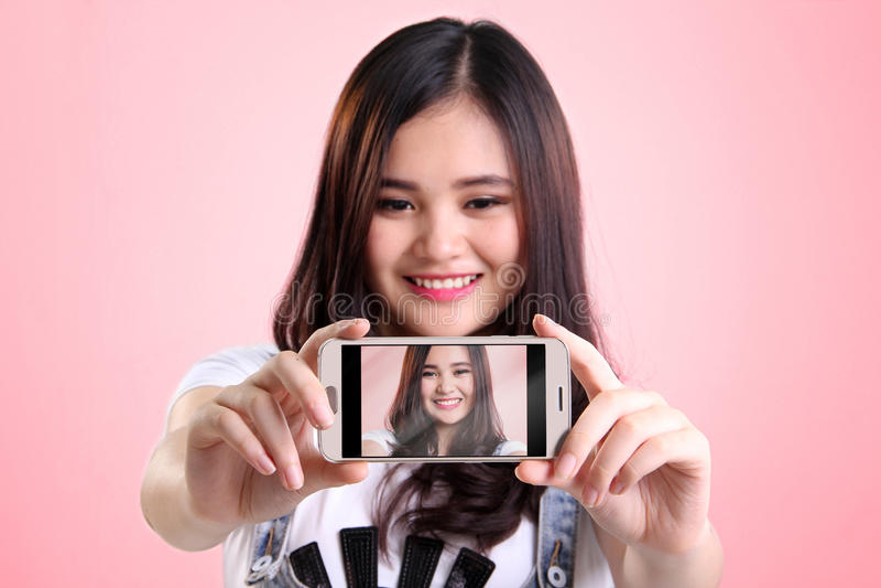 Cute selfie on smartphone screen. Self shot picture on smartphone screen of cute Asian girl, over pink background stock photos