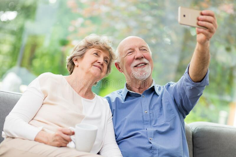 Cute couple taking selfie at home for social media. Cute senior couple taking selfie at home for social media royalty free stock photos