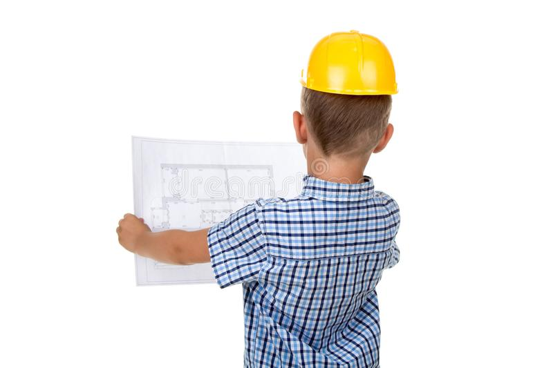 Cute serious builder boy is reading a building paper plan, turned back, isolated on white stock image