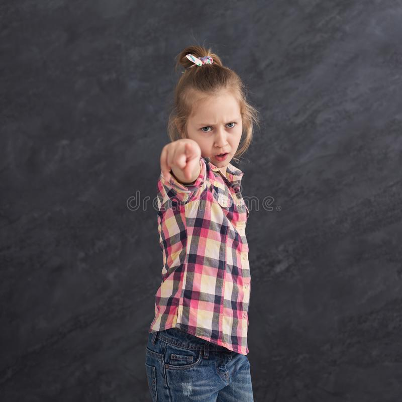 Serious little girl pointing on camera at grey background stock photos