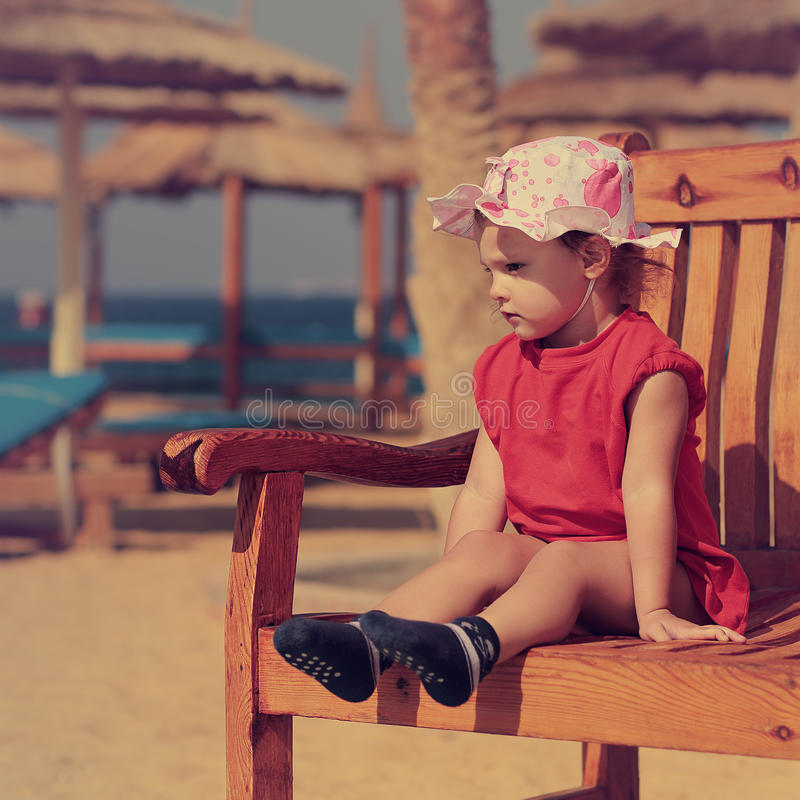 Cute serious kid girl in hat sitting on the bench royalty free stock image