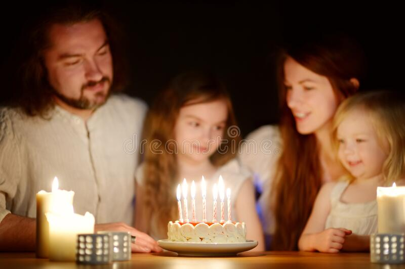 Cute sever year old girl making a wish before blowing candles on her birthday cake. Child celebrating her birhday royalty free stock images